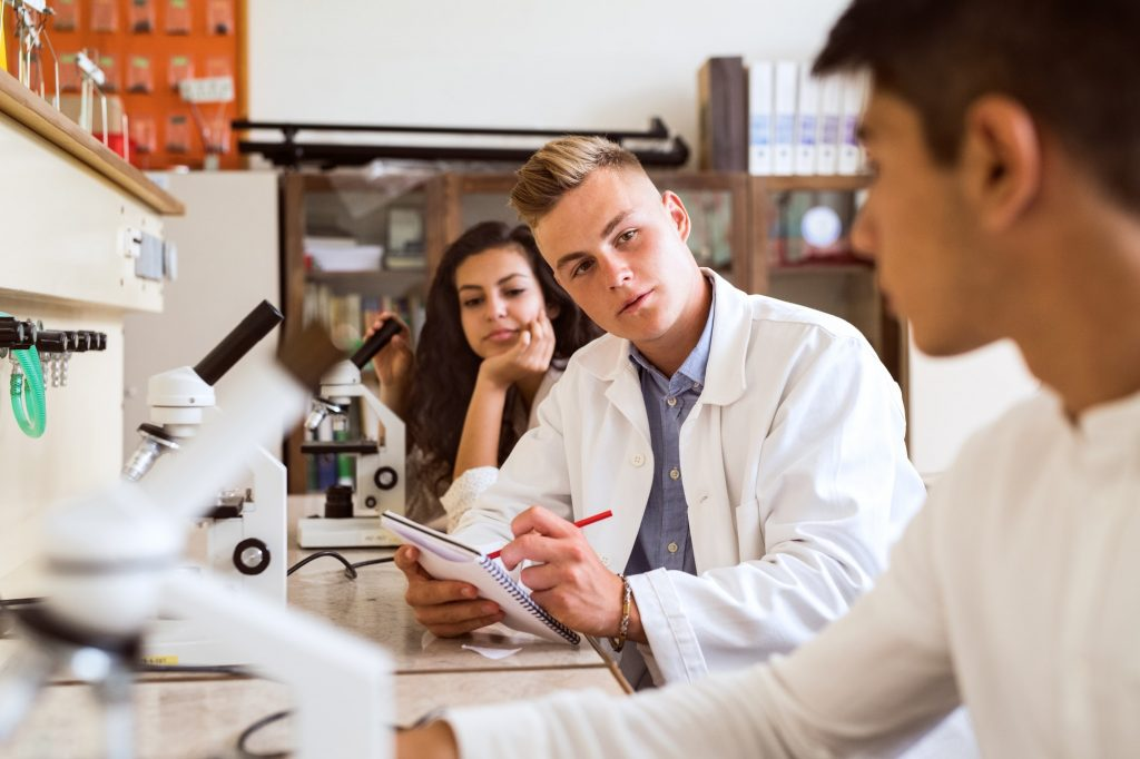 High school student with microscopes in laboratory.