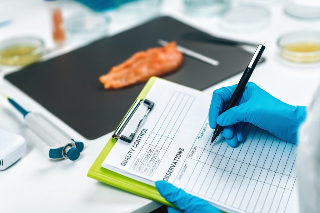 Food Safety and Quality Management. Inspector Filling Out Quality Control Form in a Laboratory